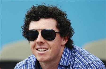 Golfer Rory McIlroy of Northern Ireland watches as his girlfriend Caroline Wozniacki of Denmark plays Ksenia Pervak of Kazakhstan during their women's singles match at the Brisbane International tennis tournament in Brisbane December 31, 2012. REUTERS/Daniel Munoz/Files