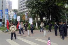 Manifestantes seguram cartazes e bandeiras nacionais ao lado de policiais diante da sede do jornal Semanário do Sul, em Guangzhou, na China. A polícia chinesa interveio para apartar brigas em frente à sede de um influente semanário de Cantão, enquanto as autoridades comunistas sinalizam uma posição mais dura contra jornalistas que desafiam a censura oficial. 08/01/2013 REUTERS/James Pomfret