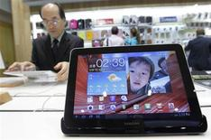 A man uses Samsung Electronics' tablet Galaxy Tab 10.1 on display for customers at the company's headquarters in Seoul in this file October 7, 2011 file photo. Samsung Electronics, the world leader in mobiles and memory chips, said it likely earned a quarterly profit of $8.3 billion, as it sold close to 500 handsets a minute and as demand picked up for the flat screens it makes for mobile devices, including those for rival Apple Inc products. REUTERS/Jo Yong-Hak/Files