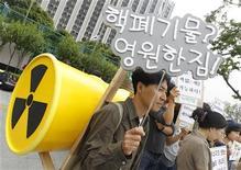 Homem carrega barril de lixo radioativo de brincadeira durante manifestação para exigir o fim das usinas nucleares, em Seul, em junho de 2011. A Coreia do Sul terá que expandir seu programa de usinas nucleares, apesar da crescente preocupação da população com questões de segurança após o desastre de 2001 em Fukushima, no Japão, e uma série de sustos que fecharam dois reatores no ano passado. 9/06/2011 REUTERS/Jo Yong-Hak