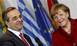 Greek Prime Minister Antonis Samaras (L) and German Chancellor Angela Merkel smile as they address the media at the Chancellery in Berlin January 8, 2013. Greece is delivering on tough economic reforms and its European partners are providing support, Prime Minister Antonis Samaras said on Tuesday during a visit to Germany. REUTERS/Fabrizio Bensch (GERMANY - Tags: POLITICS)