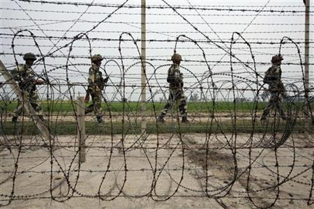 India's Border Security Force (BSF) soldiers patrol the fenced border with Pakistan near Jammu February 25, 2010. REUTERS/Mukesh Gupta/Files