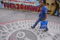Un hombre pasa junto a un mural alusivo a la figura del presidente de Venezuela, Hugo Chávez, en Caracas, ene 7 2013. El Gobierno venezolano negó el lunes que exista un vacío de poder por la prolongada ausencia de Hugo Chávez, que lucha por su vida en Cuba tras su cuarta cirugía por un cáncer, y llamó al pueblo a apoyar al presidente en las calles el 10 de enero, el día fijado por la Constitución para que asuma un nuevo mandato. REUTERS/Jorge Silva