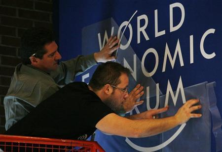 Staff adjust a logo in the Congress Centre ahead of the World Economic Forum (WEF) in Davos January 27, 2009. REUTERS/Denis Balibouse/Files