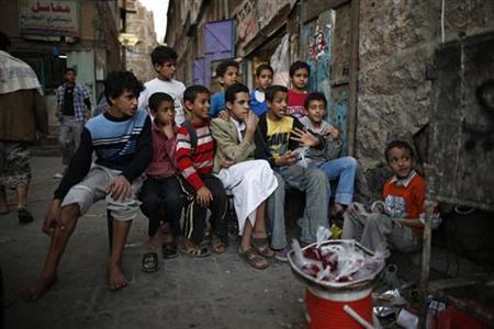 Boys watch television on a street in Old Sanaa city January 7, 2013. REUTERS/Khaled Abdullah