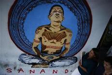 """El presidente de Venezuela, Hugo Chávez, está en Cuba desde hace casi un mes afrontando el difícil postoperatorio de su cuarta operación contra el cáncer y cada día parece menos probable que pueda regresar a su país para asumir este jueves un nuevo mandato de seis años. En la imagen, varias personas pasan junto a un dibujo en el que aparece Hugo Chávez """"sanando"""" en Caracas el 7 de enero de 2013. REUTERS/Jorge Silva"""