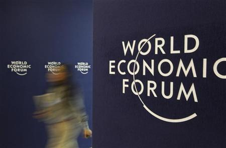 A visitor walks past WEF logo at the venue of the World Economic Forum (WEF) in Davos, January 26, 2012. REUTERS/Christian Hartmann
