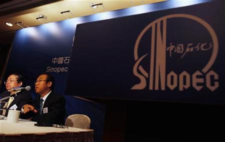 Sinopec International General Manager Li Jiangao (R) speaks beside Sinopec Chemical Commercial Holdings Vice President Zhang Guoming during a news conference in Hong Kong August 9, 2012. REUERS/Bobby Yip