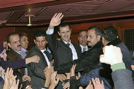 Syria's President Bashar al-Assad (C) waves to his supporters after speaking at the Opera House in Damascus January 6, 2013, in this handout photograph released by Syria's national news agency SANA. AREUTERS/Sana