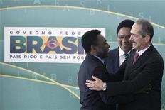 El Ministerio de Deportes de Brasil dijo que 54 jugadores o sus herederos recibirían una prima de 100.000 reales brasileños (37.000 euros) y también se les concedería una pensión mensual de 3.916 reales brasileños. En la imagen de archivo, Pelé (izq) saluda al ministro de Deportes, Aldo Rebelo. REUTERS/Ueslei Marcelino