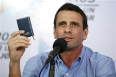 El gobernador del estado venezolano de Miranda, Henrique Capriles, sostiene una copia de la constitución nacional durante una conferencia de prensa en Caracas, ene 8 2013. La oposición venezolana pidió a los presidentes de América Latina que no avalen la intención del Gobierno de demorar la asunción de Hugo Chávez, que debería juramentarse esta semana pero sigue hospitalizado en Cuba por el cáncer que padece, y exigió a la justicia que defina la situación. REUTERS/Jorge Silva