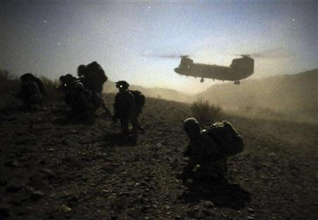 U.S. and Afghan soldiers take a knee near a U.S. Army Chinook during an operation near the town of Walli Was in Paktika province November 1, 2012. Picture taken November 1. REUTERS/Goran Tomasevic