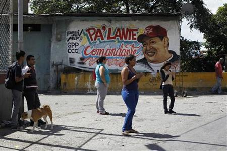 People stand in front of a mural depicting Venezuela's President Hugo Chavez in Caracas January 8, 2013. REUTERS/Carlos Garcia Rawlins