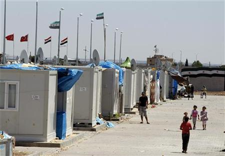 Syrian refugees stroll at a refugee camp named ''Container City'' on the Turkish-Syrian border in Oncupinar in Kilis province, southern Turkey July 3, 2012. REUTERS/Osman Orsal