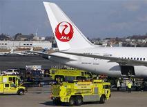 Bombeiros cercam o avião da Japan Airlines, um Boeing 787 Dreamliner que pegou fogo na segunda-feira no Aeroporto Internacional Logan, em Boston, nos Estados Unidos. 07/01/2013 REUTERS/Brian Snyder