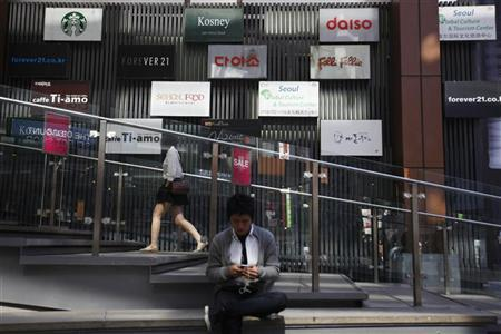 A man uses his mobile phone in front of advertisement boards in central Seoul October 11, 2012. REUTERS/Kim Hong-Ji