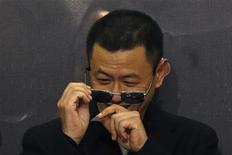 """Hong Kong director Wong Kar-Wai removes confetti from his sunglasses after he beats a drum with cast members at the premiere of the movie """"The Grandmaster"""" in Hong Kong January 8, 2013. REUTERS/Tyrone Siu"""