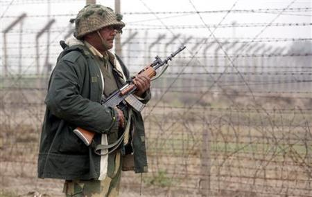 A Border Security Force (BSF) soldier patrols near the fenced border with Pakistan in Suchetgarh, southwest of Jammu, January 20, 2010. REUTERS/Mukesh Gupta/Files