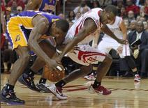 Metta World Peace des Los Angeles Lakers (à gauche) à la lutte avec Toney Douglas des Houston Rockets. Les Lakers ont enregistré mardi soir sur le parquet leur 19e défaite de la saison de NBA (125-112) pour 15 victoires seulement. /Photo prise le 8 janvier 2012/REUTERS/Richard Carson