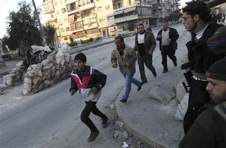 Residents run to take cover as Free Syrian Army fighters take their position behind sandbags during clashes with forces loyal to Syria's President Bashar al-Assad in Aleppo's Bustan al-Qasr district in this December 30, 2012 file photo. REUTERS/Muzaffar Salman/Files