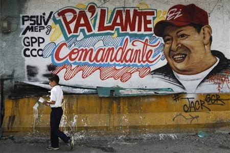 A child walks past a mural depicting Venezuela's President Hugo Chavez in Caracas January 8, 2013. Venezuela's opposition has accused the government of violating the constitution by proposing to delay cancer-stricken President Chavez's inauguration Thursday for a new term amid growing uncertainty over the polarized OPEC nation's political future. The mural reads, ''Go ahead commandant''. REUTERS/Carlos Garcia Rawlins (VENEZUELA - Tags: POLITICS HEALTH)