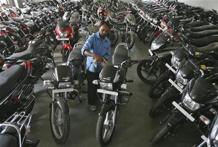A worker cleans a Hero Splendor motorcycle at a Hero MotoCorp showroom in Jammu October 23, 2012. REUTERS/Mukesh Gupta/Files