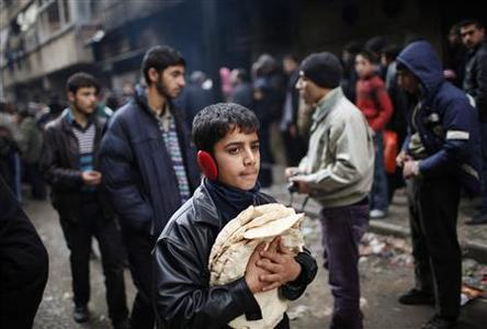 A boy holds pita bread as others stand in line outside a bakery in Aleppo in this December 21, 2012 file photo. REUTERS/Ahmed Jadallah/Files