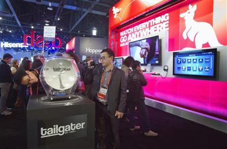 Show attendees look over a Tailgater satellite dish at the Dish Network booth during the first day of the Consumer Electronics Show (CES) in Las Vegas January 8, 2013. REUTERS/Steve Marcus