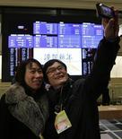 El Índice Nikkei subió el miércoles por una entrada en las empresas exportadoras ante un freno en la subida del yen que persuadió a los inversores a comprar acciones como Toyota Motor y Honda Motor. En la imagen, un inversor privado y su mujer posan frente los tableros electrónicos de la Bolsa de Japón tras la ceremonia de apertura por el año nuevo, en Tokio, el 4 de enero de 2013.REUTERS/Toru Hanai