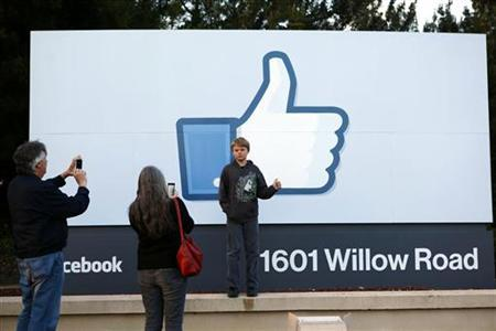 Xavier Schmidt of Menlo Park, has his picture taken by his parents outside Facebook's headquarters in Menlo Park, California, the night before the company's IPO launch, May 17, 2012. REUTERS/Beck Diefenbach/Files