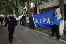 A policemen walks past as supporters of Southern Weekly demonstrate outside the office of the liberal newspaper in the southern Chinese city of Guangzhou January 9, 2013. REUTERS/Bobby Yip