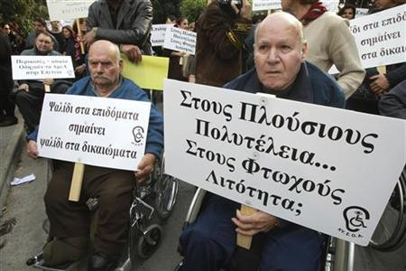People on wheelchairs demonstrate outside Cyprus' parliament, December 12, 2012. Cyprus slashed state spending on benefits on Wednesday in a bid to convince prospective international lenders it would stick to its side of an austerity bargain in a multi-billion euro bailout. REUTERS/Andreas Manolis (CYRPUS - Tags: POLITICS BUSINESS)