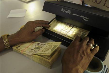 A cashier checks Indian currency notes inside a bank in Agartala July 24, 2009. REUTERS/Jayanta Dey/Files