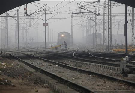 A labourer pushes a handcart past a train as he crosses railway tracks on a foggy and cold winter morning in New Delhi January 7, 2013. REUTERS/Mansi Thapliyal