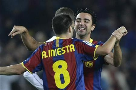 Barcelona's player Xavi Hernandez (R) celebrates Andres Iniesta's goal against Valencia during their Spanish first division soccer match at Nou Camp stadium in Barcelona, October16, 2010. REUTERS/Gustau Nacarino/Files