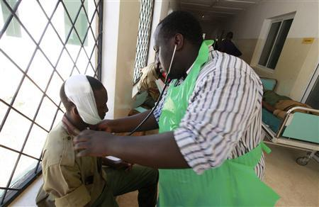 A paramedic at the Malindi district hospital attends to a policeman injured when rival communities clashed in Tana River district in the Tana Delta region, January 9, 2013. At least 100 raiders armed with guns, machetes, spears, bows and arrows attacked a village in Kenya's coastal region on Wednesday and killed six people including a woman, police said, two weeks after a similar attack that left 39 people dead in the region. REUTERS/Joseph Okanga