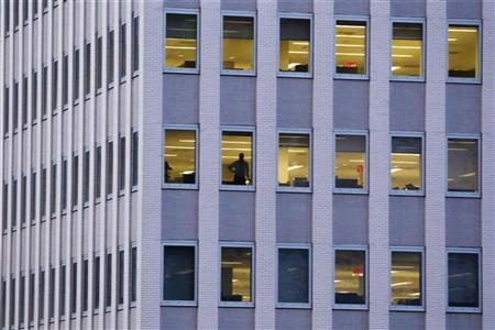 A man is seen in an office window in New York, May 1, 2012. REUTERS/Lucas Jackson