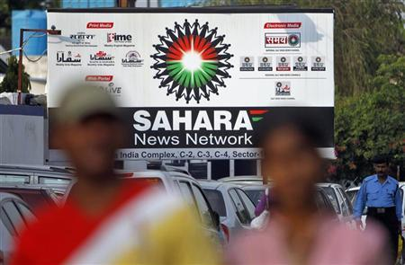 Commuters walk past a billboard advertising the Sahara News Network, along a road in Noida on the outskirts of New Delhi September 20, 2012. REUTERS/Mansi Thapliyal/Files