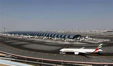 A plane passes next to the Emirates Airlines terminal at the concourse in Dubai International Airport, January 7, 2013. REUTERS/Jumana El Heloueh