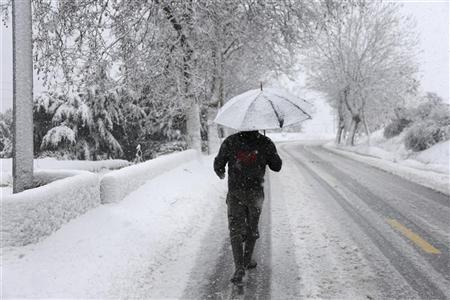 A resident is seen walking through the snow covered main highway linking Beirut to Damascus after a heavy snowstorm in Sawfar village, eastern Lebanon January 8, 2013. REUTERS/ Mohamed Azakir