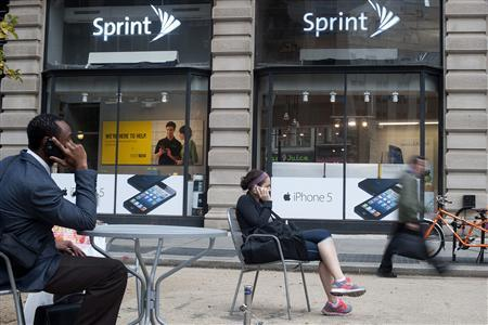 People talk on their cell phones as passers-by walk past a Sprint store in New York, in this October 15, 2012 file picture. Dish Network put in a bid for Clearwire Corp on January 8, 2013 which could trump Sprint Nextel's $2.2 billion offer and set the stage for a takeover battle over a wireless service provider that owns crucial mobile spectrum. REUTERS/Keith Bedford/File