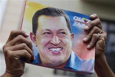Imagen de archivo de un partidario del presidente de Venezuela, Hugo Chávez, con un afiche con su rostro durante la inauguración de la Asamblea Nacional en Caracas, ene 5 2013. El Gobierno venezolano pospuso el martes indefinidamente la juramentación del presidente Hugo Chávez a causa del complicado postoperatorio que enfrenta en Cuba, en una nueva señal de que su delicado estado de salud podría alejarlo finalmente del poder. REUTERS/Carlos Garcia Rawlins