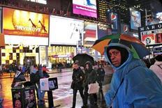 Unas personas se protegen de una lluvia en Times Square, Nueva York, dic 26 2012. Las fuertes lluvias previstas para la próxima semana en la región del Delta del río Misisipi y el sudeste de Estados Unidos ofrecerán cierto alivio tras la peor sequía en más de 50 años en el país, dijo el miércoles un meteorólogo agrícola. REUTERS/Eduardo Munoz