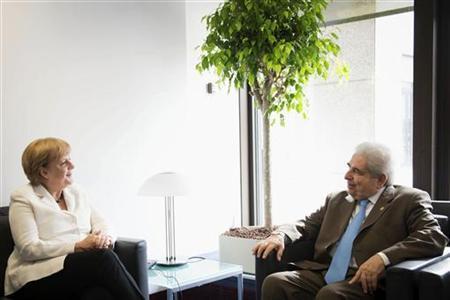 German Chancellor Angela Merkel (L) talks with Cyprus' President Demetris Christofias at an European Union leaders summit in Brussels June 29, 2012. REUTERS/Bundesregierung/Guido Bergmann/Pool (BELGIUM - Tags: POLITICS BUSINESS)