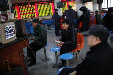 Investors look at computer screens showing stock information at a brokerage house in Shanghai January 4, 2013. REUTER/Aly Song (CHINA - Tags: BUSINESS)