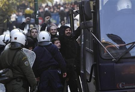 Occupiers of ''Villa Amalia'' acknowledge supporters as they are escorted into a police bus in Athens January 9, 2013. REUTERS/John Kolesidis