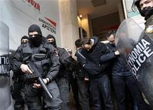 La policía griega arrestó a cien personas el miércoles en una casa ocupada en Atenas popular entre los grupos antisistema y extremistas de izquierda, lo que llevó a los manifestantes a entrar en las oficinas de un partido de la coalición de gobierno. En la imagen, unos ocupas detenidos por la policía en Atenas, el 9 de enero de 2013. REUTERS/John Kolesidis