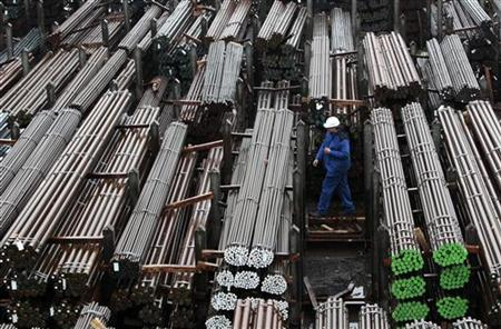 A workers walks through finished steel bars of different quality and size outside at the steel mill of German steel maker Lech-Stahlwerke GmbH in Meitingen near Augsburg October 9, 2012. REUTERS/Michaela Rehle (GERMANY - Tags: BUSINESS COMMODITIES)