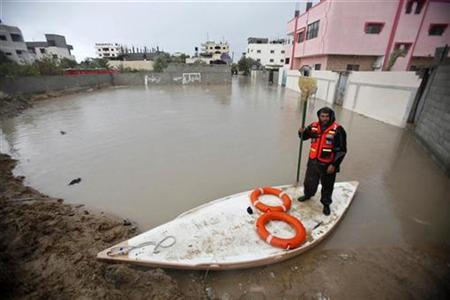 A member of Palestinian civil defense rides in a boat through a flooded area caused by heavy rain in Rafah in the southern Gaza Strip January 9, 2013. REUTERS/Ibraheem Abu Mustafa