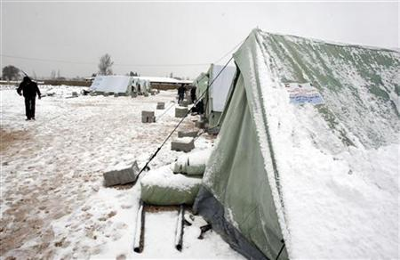 Syrian refugees stand in snow outside their tents during a winter storm in al-Marj, in the Bekaa valley January 9, 2013. The worst winter storm in two decades has hit the eastern Mediterranean this week, bringing destruction and death to Syria and its neighbours who are already dealing with a refugee crisis from the country's civil war. REUTERS/Afif Diab